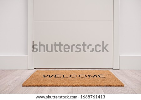 White door with a welcome mat Royalty-Free Stock Photo #1668761413