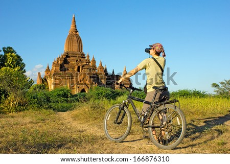 girl photographer on a bicycle takes a picture of the temple in Bagan, Myanmar(Burma)