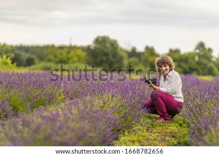 Happy woman takes a picture in a lavender field in Poland.