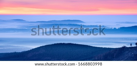 View from Mount Brocken over endless forest at sunrise, valleys filled with morning fog, Harz National Park, Germany #1668803998