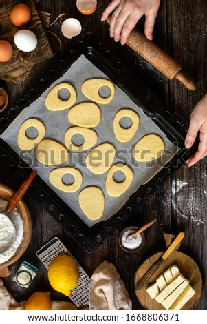 overhead shot of baked egg shaped easter cookies on baking tray on rustic wooden table with flour, eggs, butter, lemon. process of baking cookies. easter card #1668806371