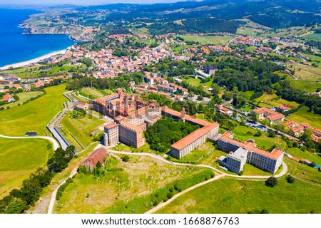 Picturesque aerial view of green valleys on Cantabrian Sea coastal area with brownish roofs of houses of Comillas village, Spain #1668876763