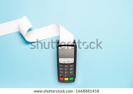 pos terminal with long cash register tape on blue background. shopping theme Royalty-Free Stock Photo #1668881458