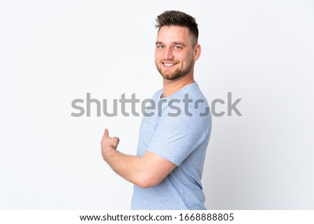 Russian handsome man over isolated background pointing back #1668888805