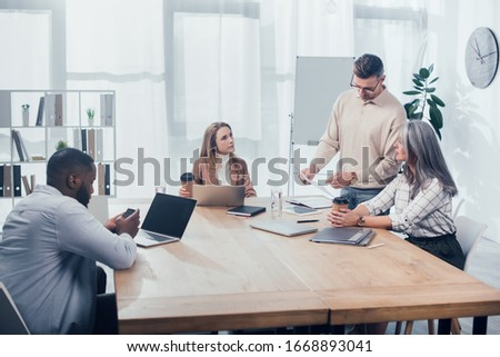 colleagues doing paper work and african american man using smartphone #1668893041