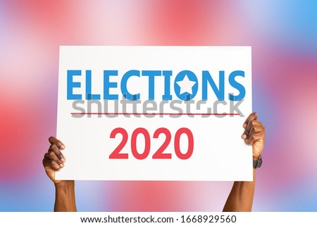 African American citizen holding sign that says ELECTIONS 2020 on colorful background, closeup of hands