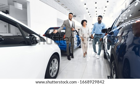 Car Selling Business. Manager Showing Luxury Automobile To Afro Spouses In Automobile Dealership Center. Panorama #1668929842