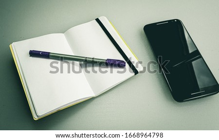 A closeup shot of a notebook with a grey and purple pen on it next to a phone #1668964798