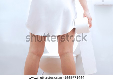 Women wearing white sleepwear, standing in the toilet, Holding a toilet paper ,health care concept #1668971464
