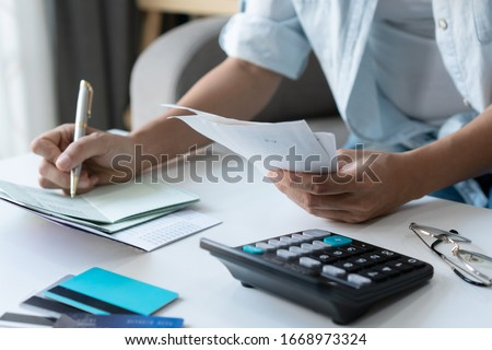 Pretty young Asian woman using a pen writing on bank account book while holding the bills to calculate in living room at home. Expenses, account, taxes, home budget concept.  #1668973324