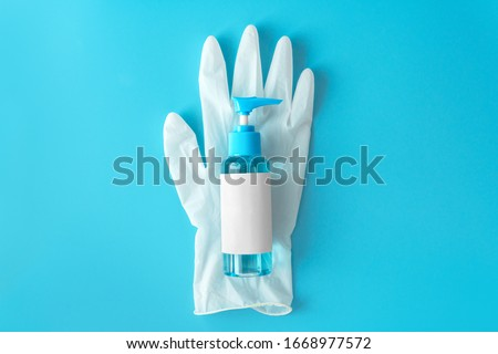 Top down view blue alcohol liquid for medical purpose and Anti coronavirus COVID-19 (Ethanol or ethyl alcohol) in a plastic press pump head blue bottle with blank label on white disposable glove.  #1668977572