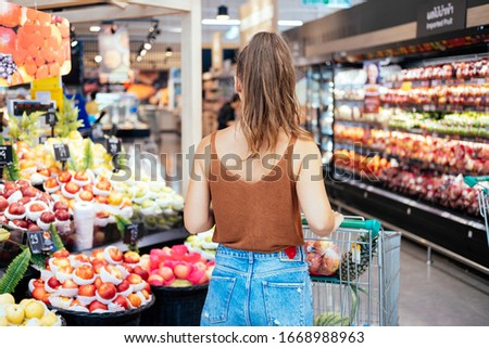 Unrecognizable woman pushes shopping cart in supermarket stock photo. Young woman groceries shopping in local supermarket at fruit department