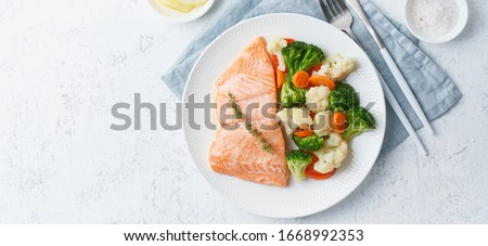 Steam salmon and vegetables, Paleo, keto, fodmap, dash diet. Mediterranean diet with steamed fish. Healthy concept, white plate on gray table, gluten free, lectine free, top view, long banner Royalty-Free Stock Photo #1668992353