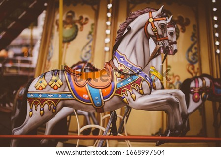 Retro carousel white / black horse. Old wooden horse carousel. Carousel! Horses on vintage, retro carnival cheerful walk. CloseUp of colorful carousel with horses. vintage photo processing Royalty-Free Stock Photo #1668997504