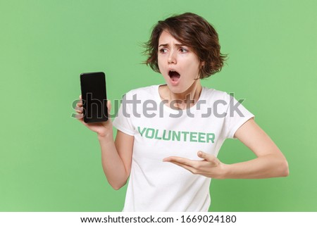 Worried young woman in volunteer t-shirt isolated on pastel green background. Voluntary free work assistance help charity grace teamwork concept. Pointing hand on mobile phone with blank empty screen
