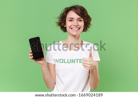Smiling woman in volunteer t-shirt isolated on pastel green background. Voluntary free work assistance help charity grace teamwork concept. Hold mobile phone with blank empty screen, showing thumb up