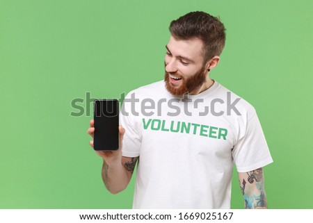 Surprised bearded man in white volunteer t-shirt isolated on pastel green background. Voluntary free work assistance help charity grace teamwork concept. Hold mobile phone with blank empty screen