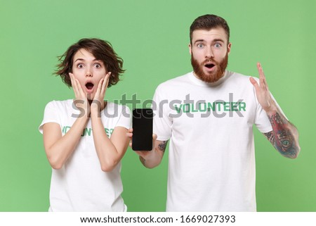 Amazed two young friends couple in white volunteer t-shirt isolated on green background. Voluntary free work assistance help charity grace teamwork concept. Hold mobile phone with blank empty screen