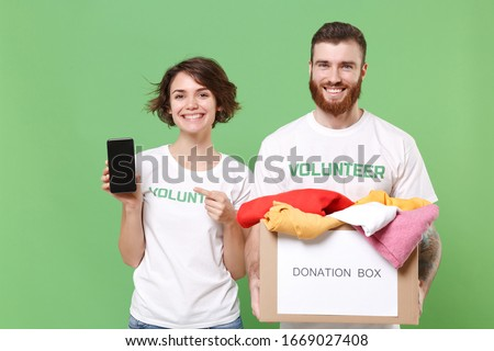 Smiling friends couple in volunteer t-shirt isolated on green background. Voluntary free work assistance help charity grace teamwork. Hold donation box with clothes, mobile phone with empty screen