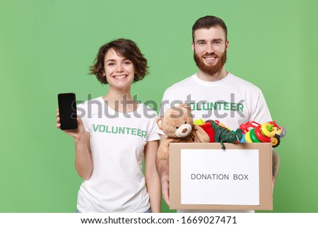 Smiling friends couple in volunteer t-shirt isolated on green background. Voluntary free work assistance help charity grace teamwork. Hold donation box with kids toys, mobile phone with blank screen