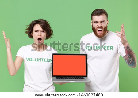 Irritated friends couple in white volunteer t-shirt isolated on green background. Voluntary free work assistance help charity grace teamwork concept. Hold laptop pc computer with blank empty screen