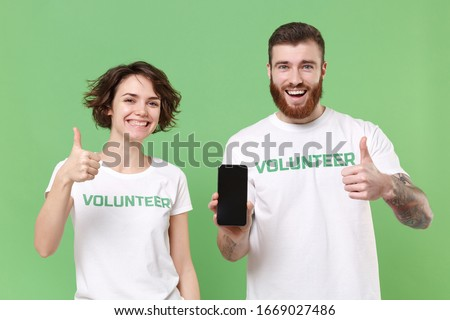 Smiling friends couple in volunteer t-shirt isolated on green background. Voluntary free work assistance help charity grace teamwork concept. Hold mobile phone with empty screen, showing thumbs up