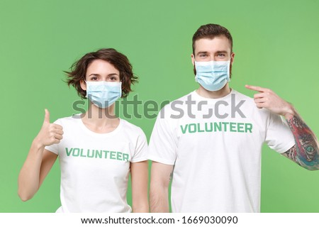 Two young friends couple in volunteer t-shirt isolated on pastel green background. Voluntary free work assistance help charity grace teamwork. Point index finger on sterile face mask showing thumb up #1669030090