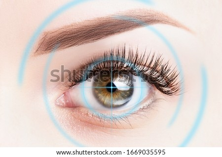 Refractive surgery, eye laser surgery concept. Female eye close up with blue laser rays. #1669035595