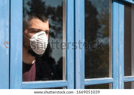 Coronavirus. Sick man of corona virus  looking through the window and wearing mask protection and recovery from the illness in home. Quarantine. Patient isolated to prevent infection. Lockdown #1669051039