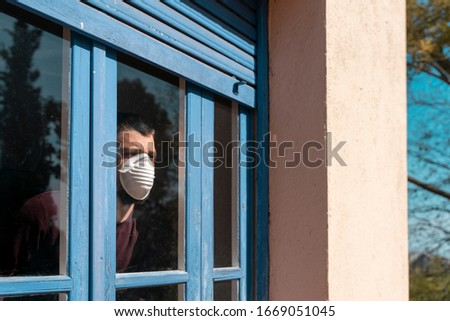 Coronavirus. Sick man of corona virus  looking through the window and wearing mask protection and recovery from the illness in home. Quarantine. Patient isolated to prevent infection. Lockdown #1669051045