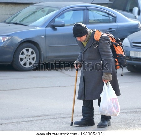 A homeless tramp with a stick walks through the Parking lot, Bolshevikov Avenue, Saint Petersburg, Russia, March 2020 #1669056931