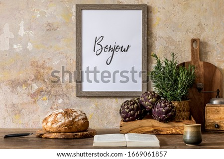 Stylish composition of kitchen interior with wooden mock up frame, family table, vegetables, bread, book, cup of coffee, herbs and kitchen accessories in wabi sabi concept of home decor.