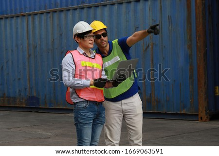 Foreman or Supervisor in uniform and wearing yellow safety helmet checking cargo  from Cargo ship freight for import export with laptop  Business logistic concept. #1669063591
