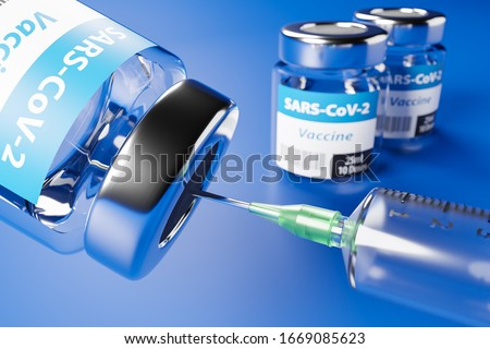 Vaccination against the new Corona Virus SARS-CoV-2: Two glass containers with 10 doses each and a syringe in front. Selective focus on foreground. Royalty-Free Stock Photo #1669085623