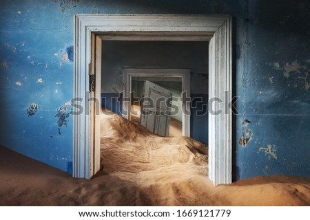 Abandoned building and the door being taken over by encroaching sand, Kolmanskop ghost town, Namib Desert Royalty-Free Stock Photo #1669121779