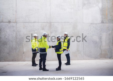 Group of engineers standing on construction site, shaking hands. #1669122565