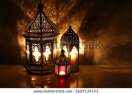 Ornamental Arabic lanterns. Burning candles on table glowing at night. Festive greeting card, invitation for Muslim holy month Ramadan Kareem. Iftar dinner background with golden glow. #1669134151