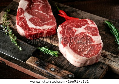 Raw rib eye steak of beef on a wooden Board with a meat cleaver and seasonings #1669173181