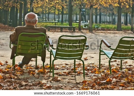 Оld man sitting alone on park bench under tree/ Autumn landscape/ Loneliness/ Faceless Royalty-Free Stock Photo #1669176061
