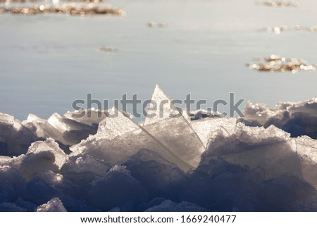 Ice on the edge of the coastline against the background of water. Thin ice near the shore of the river with side lighting. Autumn ice drift. Floating ice floes. #1669240477