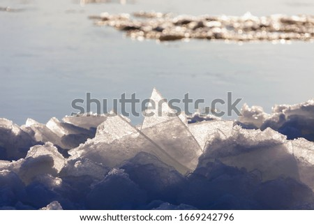Coastal ice on the background of water. Thin ice near the shore of the reservoir in the evening sun. Autumn ice drift. Floating ice floes. #1669242796