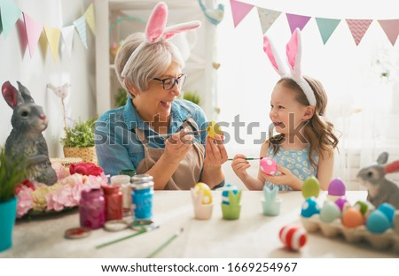 Happy easter! A grandmother and her granddaughter painting Easter eggs. Happy family preparing for Easter. Cute little child girl wearing bunny ears on Easter day. #1669254967