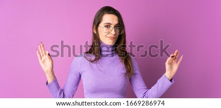 Young woman over isolated purple background in zen pose #1669286974