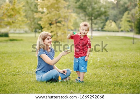 Young Caucasian mother and boy toddler son blowing soap bubbles in park. Mom and child playing having fun together outdoor on summer day. Happy authentic family childhood lifestyle.  #1669292068