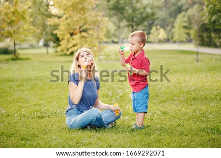Young Caucasian mother and boy toddler son blowing soap bubbles in park. Mom and child playing having fun together outdoor on summer day. Happy authentic family childhood lifestyle.  #1669292071