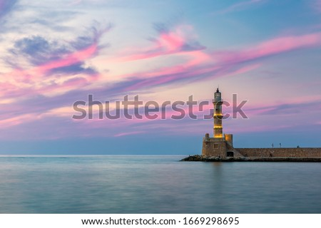 Venetian harbour and lighthouse in old harbour of Chania at sunset, Crete, Greece. Old venetian lighthouse in Chania, Greece. Lighthouse of the old Venetian port in Chania, Greece. #1669298695