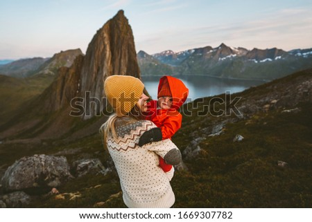 Mother hiking with baby family vacation adventurous travel outdoor in mountains woman with child together trip in Norway recreation healthy lifestyle  #1669307782