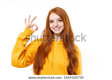 Smiling young redhead woman girl in casual yellow hoodie posing isolated on white wall background studio portrait. People sincere emotions lifestyle concept. Mock up copy space. Showing Ok gesture #1669320730