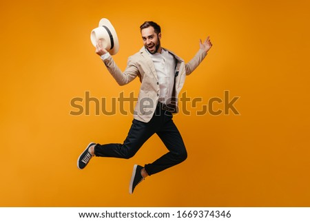 Stylish guy takes off hat and jumps high on isolated background #1669374346