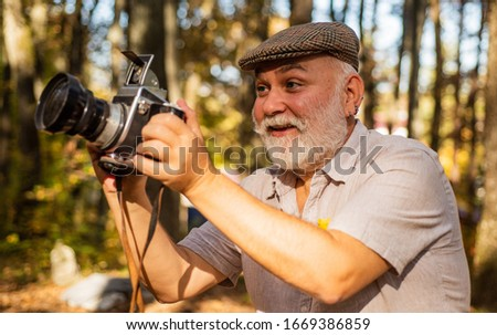 Look at this. Happy pensioner hold camera in nature. professional photographer with camera. The photographer hold DSLR camera. makes beautiful pictures on film retro camera. freedom man traveler.